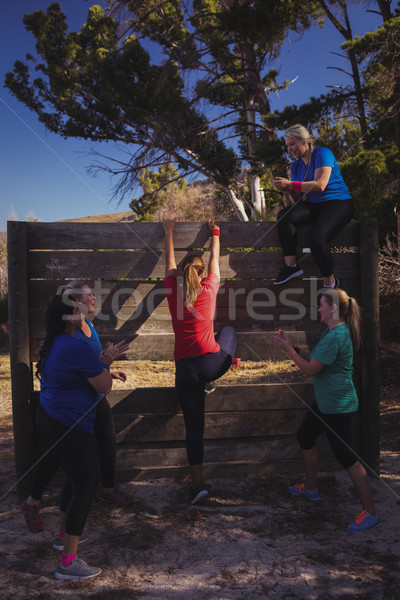 Woman being cheered by her teammates to climb a wooden wall during obstacle course training Stock photo © wavebreak_media