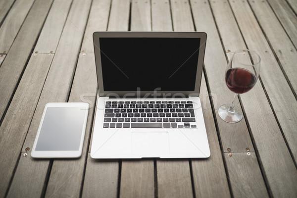 Laptop digitális tabletta borospohár keményfa padló veranda Stock fotó © wavebreak_media