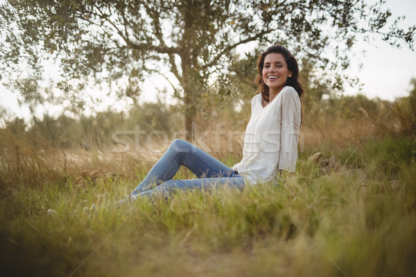 Glimlachend jonge vrouw vergadering grasachtig veld boerderij Stockfoto © wavebreak_media