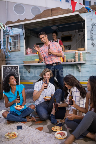 Group of friends drinking beer while having lunch Stock photo © wavebreak_media
