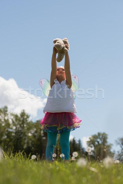 Mosolyog lány játszik plüssmaci park virág Stock fotó © wavebreak_media