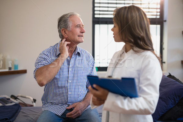Senior male patient showing neck sprain to female doctor with file Stock photo © wavebreak_media