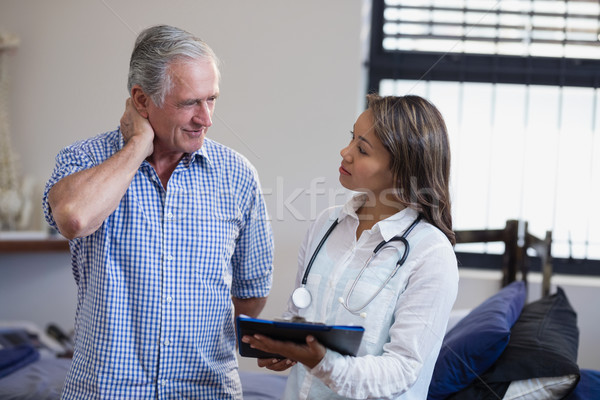 Senior male patient and female therapist discussing file against window Stock photo © wavebreak_media