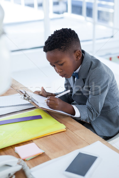Businessman writing on paper attached to clipboard Stock photo © wavebreak_media