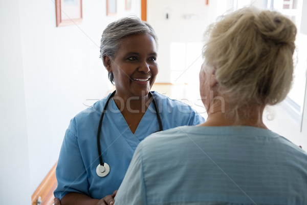Senior woman and nurse talking while standing in corridor Stock photo © wavebreak_media
