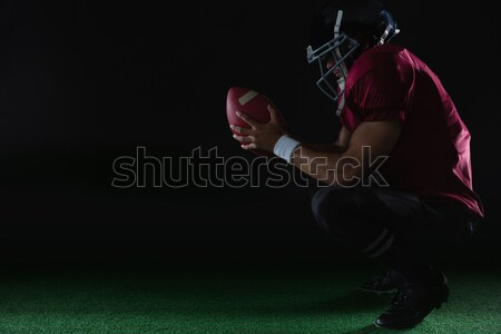 American football player sitting on toes holding a ball with both his hands Stock photo © wavebreak_media