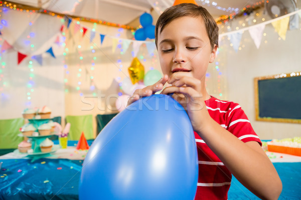 Cute boy holding blue balloon during birthday party Stock photo © wavebreak_media