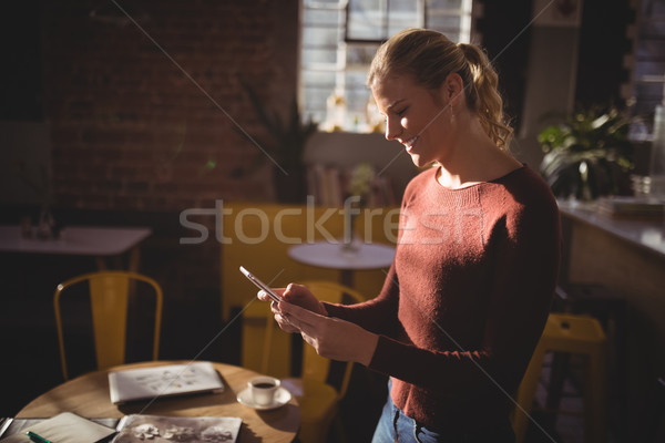 Smiling young blond woman using smartphone at coffee shop Stock photo © wavebreak_media