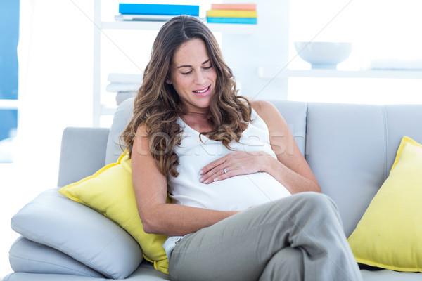 счастливым беременная женщина рук желудка гостиной женщину Сток-фото © wavebreak_media