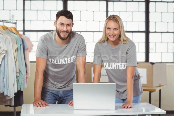 Portrait of smiling volunteers working on laptop Stock photo © wavebreak_media