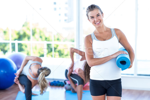 Portrait of happy woman holding yoga mat Stock photo © wavebreak_media