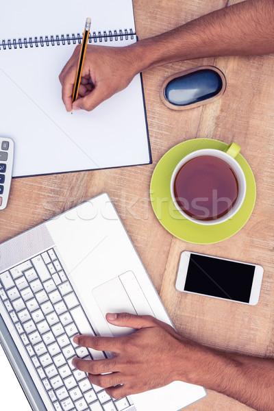Overhead view of businessman working on laptop Stock photo © wavebreak_media