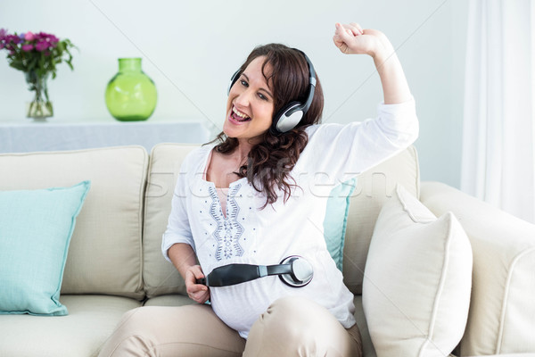 Terhes nő tart fejhallgató has nappali nő Stock fotó © wavebreak_media