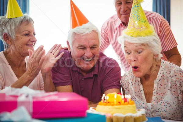 Senior woman blow on birthday cake Stock photo © wavebreak_media