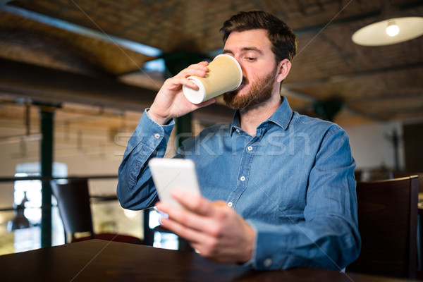 Man having coffee while text messaging on mobile phone Stock photo © wavebreak_media