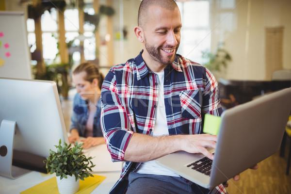 Businesman using laptop at creative office Stock photo © wavebreak_media