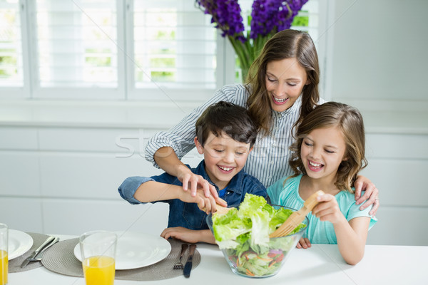 Smiling mother and childrens mixing bowl of salad in kitchen Stock photo © wavebreak_media