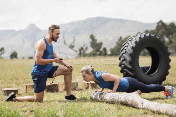 Fit performing pushup exercise while man measuring time Stock photo © wavebreak_media