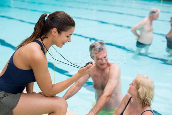 Young female trainer monitoring time of senior swimmers at poolside Stock photo © wavebreak_media