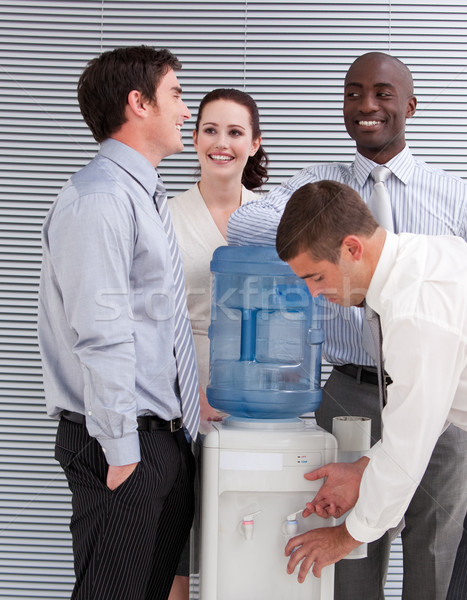 Stock photo: Smiling multi-ethnic business people interacting at a watercoole