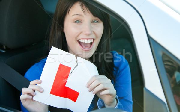 Happy brunette teen girl sitting in her car tearing a L-sign Stock photo © wavebreak_media