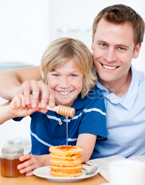 Happy boy and his father putting honey on waffles Stock photo © wavebreak_media