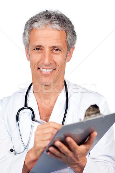 Smiling doctor writting documents Stock photo © wavebreak_media