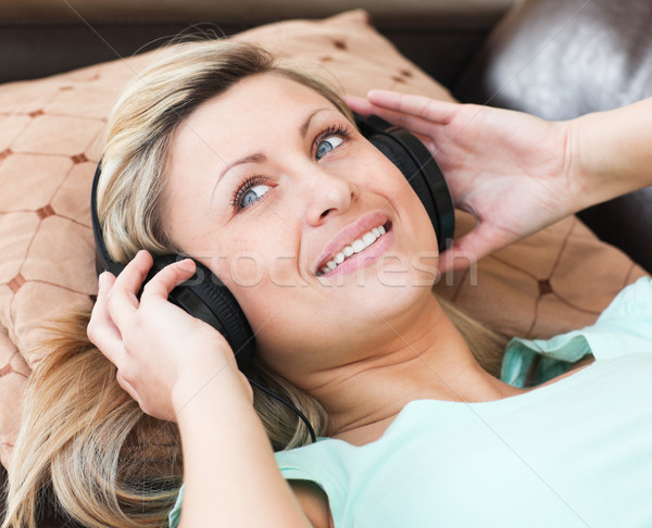 Jolly woman with headphones on lying on a sofa Stock photo © wavebreak_media