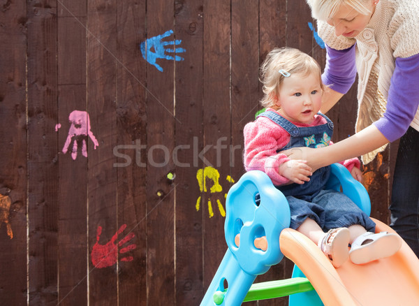 Little girl and her mother having fun with a chute at the playground  Stock photo © wavebreak_media