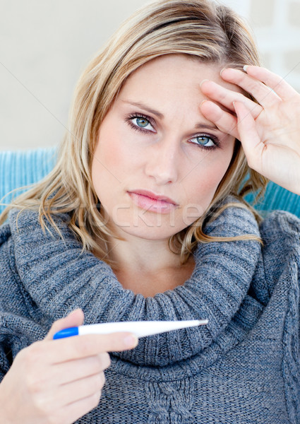 Unhappy woman taking her sick tempretaure on the sofa Stock photo © wavebreak_media
