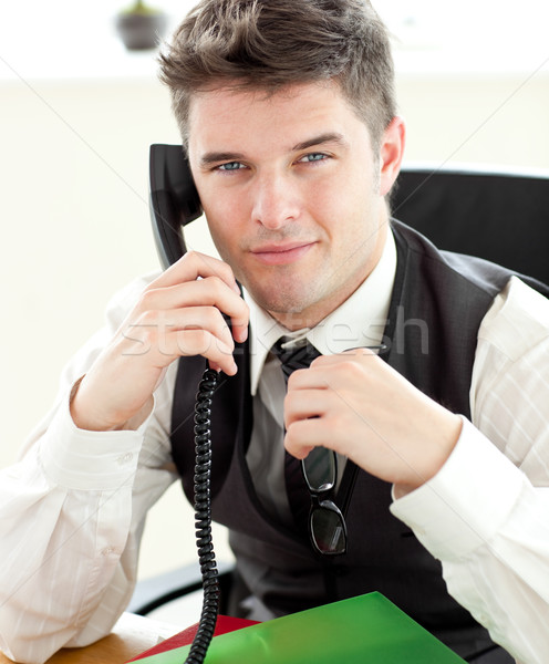 Attentive businessman talking on phone looking at the camera siiting in his office Stock photo © wavebreak_media