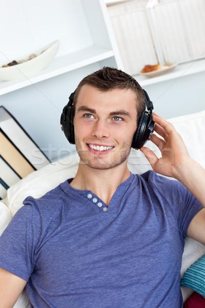Animado joven escuchar música sesión sofá salón Foto stock © wavebreak_media