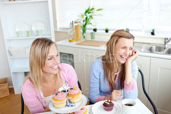 Two cheerful female friends eating pastries and drinking coffee in the kitchen Stock photo © wavebreak_media