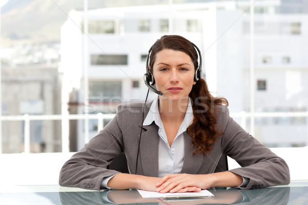 Attractive businesswoman speaking using headset sitting at a table in her office Stock photo © wavebreak_media
