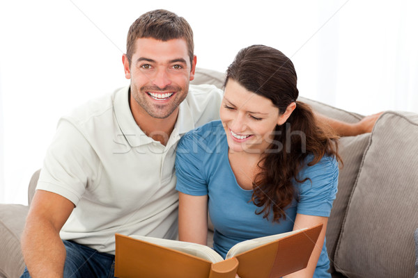 Pretty woman reading a book with her boyfriend on the sofa at home Stock photo © wavebreak_media