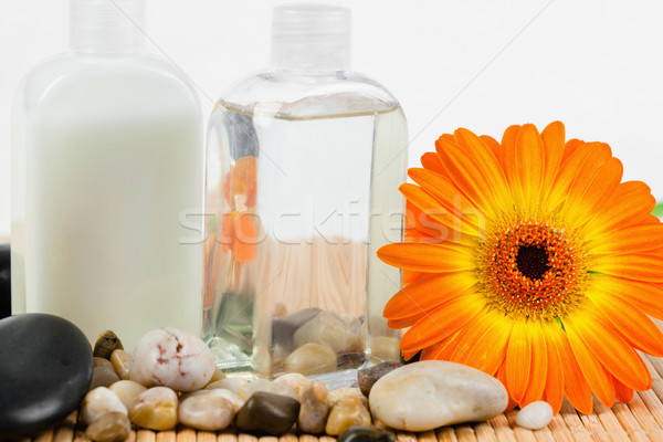 Close up of sunflower with  round smooth pebbles and glass bottles Stock photo © wavebreak_media