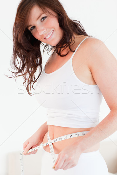 Attractive brunette woman measuring her belly with a tape measure while standing in her bedroom Stock photo © wavebreak_media
