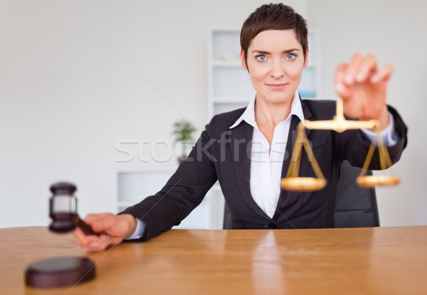 Serious woman with a gavel and the justice scale in her office Stock photo © wavebreak_media