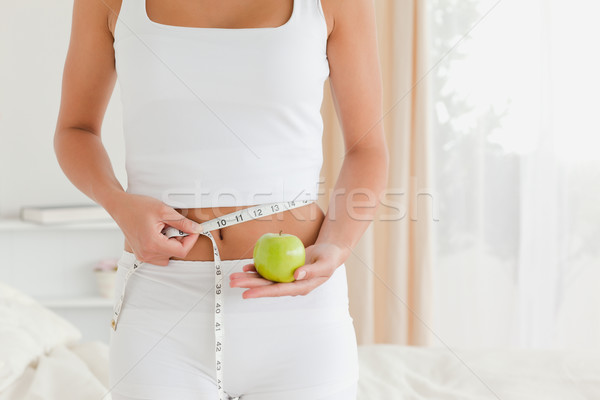 pretty woman measuring her waist while holding an apple in bedroom Stock photo © wavebreak_media