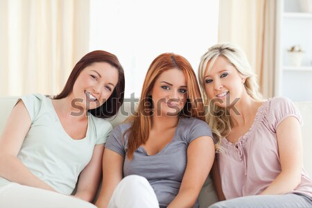 Stock photo: Joyful Women watching a movie eating popcorn in a living room