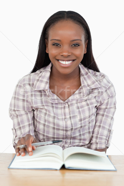 Smiling girl reading a novel against a white background Stock photo © wavebreak_media