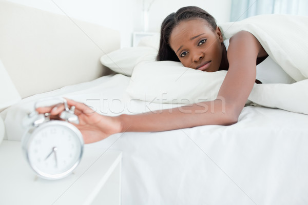 Tired young  woman switching off her alarm clock in her bedroom Stock photo © wavebreak_media