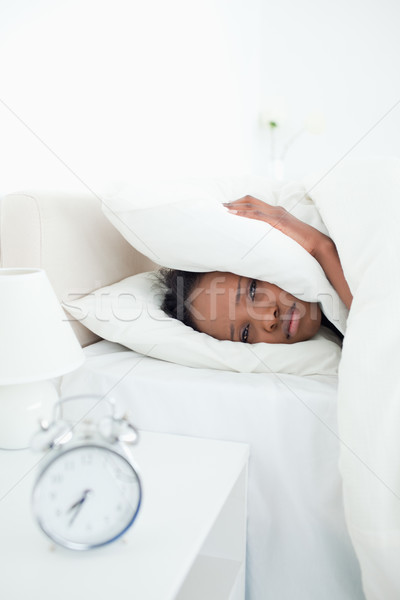 Portrait of a sad woman covering her ears while her alarm clock is ringing in her bedroom Stock photo © wavebreak_media