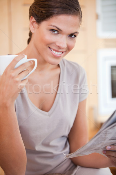 Smiling young woman reading the news while drinking coffee Stock photo © wavebreak_media