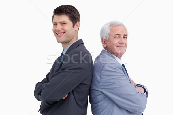 Close up of businessman and his mentor standing back to back against a white background Stock photo © wavebreak_media