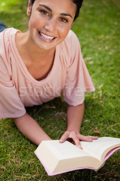 Smiling woman looking upwards while reading a book as she is lying prone on grass Stock photo © wavebreak_media