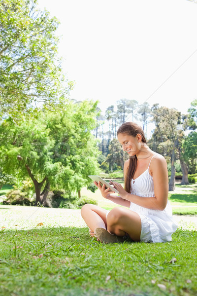 Side view of a smiling young woman on the lawn with a tablet computer Stock photo © wavebreak_media
