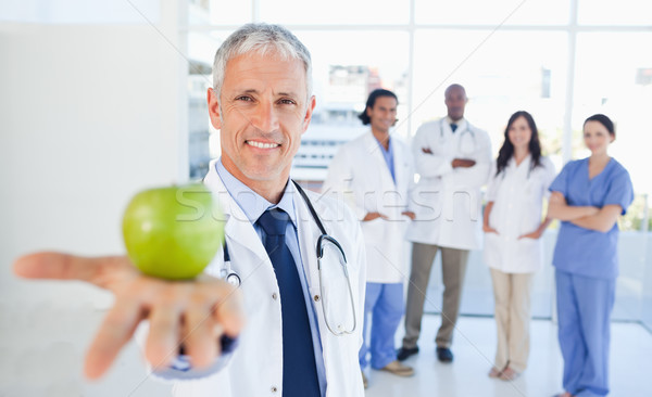Medical interns in the background looking at their doctor who is holding an apple Stock photo © wavebreak_media