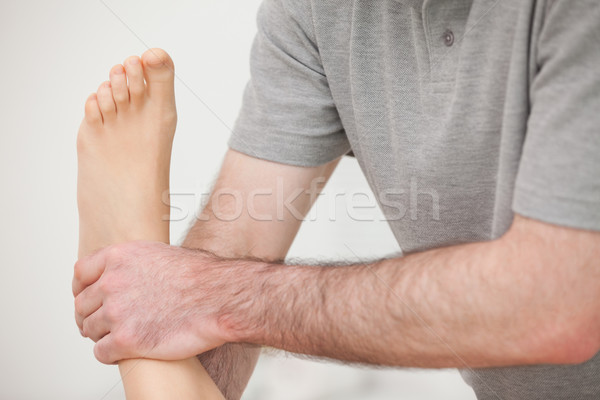 Close-up of a physiotherapist manipulating an ankle in a room Stock photo © wavebreak_media
