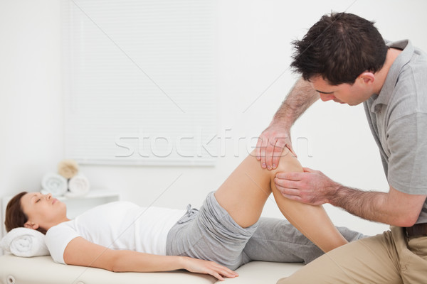 Brown-haired man massaging the knee of a woman in a room Stock photo © wavebreak_media
